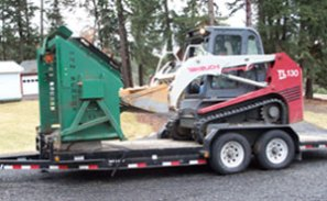Topsoil screener PVG-12v easily being loaded and unloaded off of a trailer.